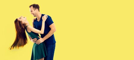 Love, relationship, dating, flirting, lovers, romantic concept - full body portrait of hugging or dancing couple, looking at each other. Yellow background.