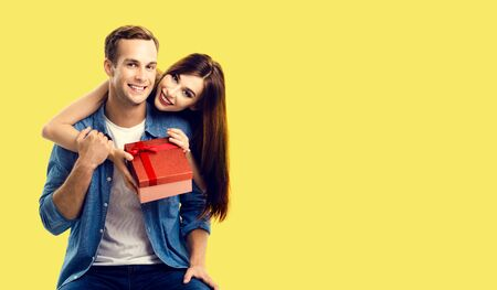 Love, relationship, dating, flirting, lovers concept - happy smiling amorous couple opening gift box. Yellow background. Copy space for some text.