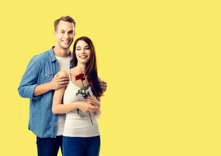 Love, relationship, dating, flirting, romantic concept - portrait of happy smiling hugging couple with flower, close to each other. Yellow background. Copy space. 스톡 콘텐츠