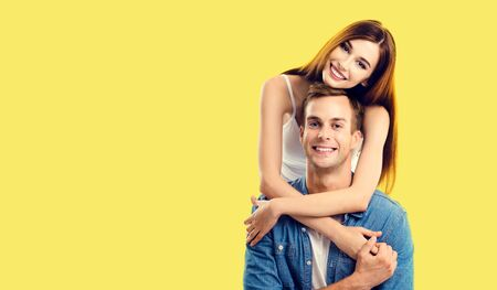 Love, relationship, dating, lovers, romantic concept - lovely couple, standing close to each other and looking at camera with smile. Yellow background. Copy space for some text.
