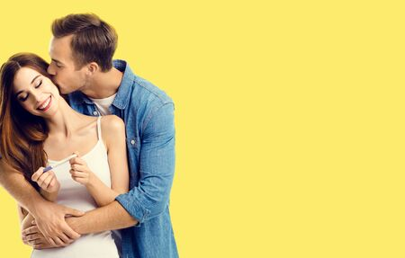 Love, relationship, happy lovers, family concept - amorous happy couple, finding out results of a pregnancy test. Yellow color background. Фото со стока - 140100501
