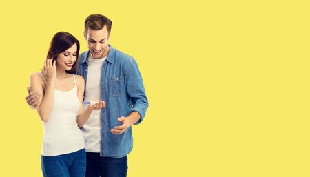 Love, new parents and happy family concept - young happy couple, finding out results of a pregnancy test. Yellow color background. Copy space for some text.