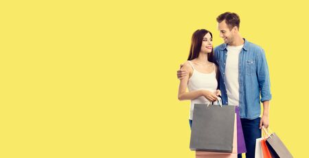 Love, holiday sales, shop, retail, consumer concept - happy couple with shopping bags, looking at each other. Yellow color background. Copy space for some text.