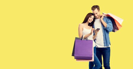 Love, holiday sales, shop, retail, consumer concept - happy couple with shopping bags, looking at mobile phone, standing close to each other. Yellow background. 스톡 콘텐츠