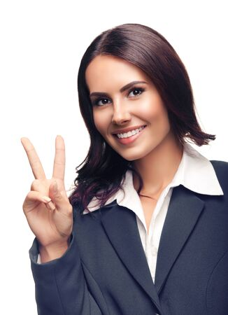Happy smiling beautiful young businesswoman in grey confident suit, showing two fingers or victory gesture, isolated against white background