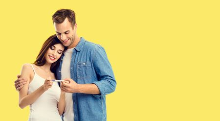 Love, relationship, new parents and happy family concept - young couple, finding out results of a pregnancy test. Yellow background. Copy space for some text.