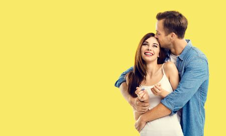 Love, new parents and family concept - very happy excited couple, finding out results of a pregnancy test. Yellow color background. Copy space for some text. 스톡 콘텐츠
