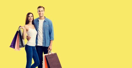 Love, holiday sales, shop, retail, consumer concept - happy couple with shopping bags, standing close to each other, and looking at camera. Yellow color background.