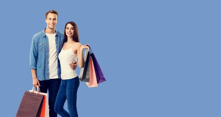 Love, holiday sales, shop, retail, consumer concept - happy couple with shopping bags, standing close to each other, and looking at camera. Blue color background.