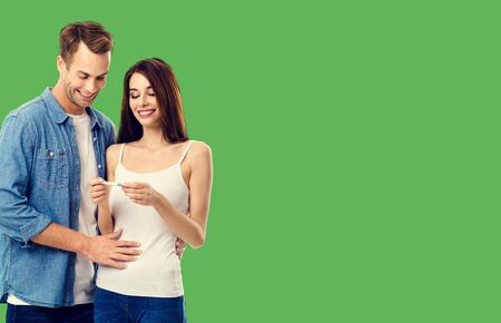 Love, relationship, new parents and happy family concept - young lovely couple, finding out results of a pregnancy test. Green color background. 스톡 콘텐츠