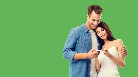 Love, relationship, new parents and happy family concept - young couple, finding out results of a pregnancy test. Green background. Copy space for some text.