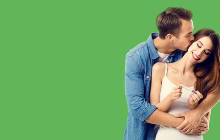 Love, relationship, happy lovers, family concept - amorous happy couple, finding out results of a pregnancy test. Green color background. 스톡 콘텐츠