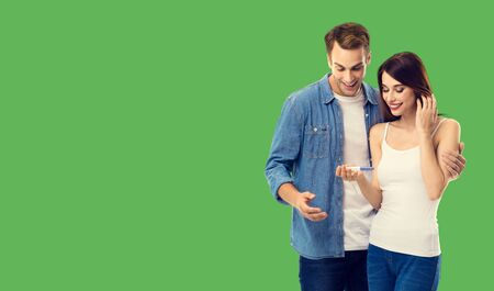Love, new parents and happy family concept - young happy couple, finding out results of a pregnancy test. Green color background. Copy space for some text.