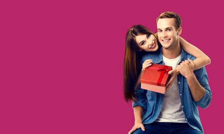 Love, relationship, dating, flirting, lovers concept - happy smiling amorous couple opening gift box. Over red color background. Copy space for some text. 스톡 콘텐츠