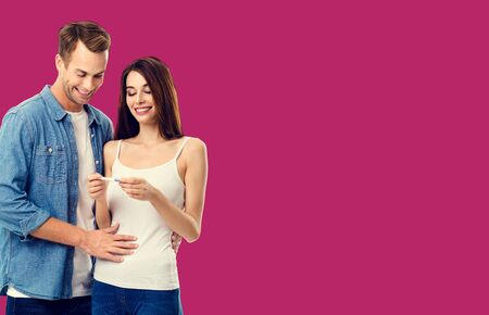 Love, relationship, new parents and happy family concept - young lovely couple, finding out results of a pregnancy test. Over red color background.