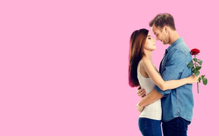 Love, relationship, dating, flirting, romantic concept - amorous hugging couple with flower, standing close to each other, against rose pink background. Copy space.