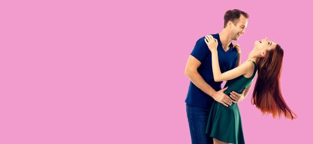 Love, relationship, dating, flirting, lovers, romantic concept - full body portrait of hugging or dancing couple, looking at each other. Over rose pink color background.