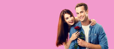 Love, relationship, dating, flirting, romantic concept - portrait picture of happy couple with flower, looking at camera. Over rose pink color background. Copy space for some text.