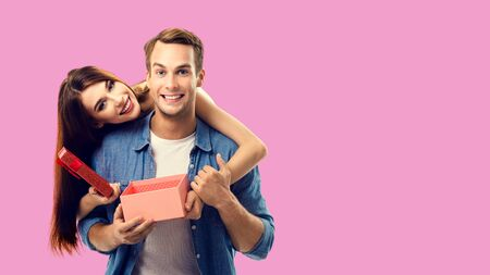 Love, relationship, dating, flirting, lovers, romantic concept - happy couple opening gift box, looking at camera. Over red color background. Copy space for some text. 스톡 콘텐츠