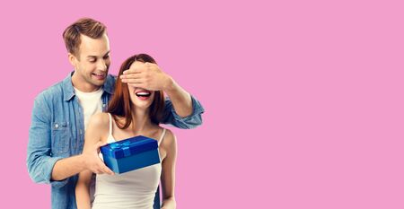 Love, dating, celebrating, lovers concept - happy amorous couple with blue gift box. Over rose pink color background. Copy space for some text.