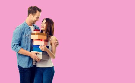 Love, relationship, dating, flirting, lovers, romantic concept - happy young couple holding gift boxes, close to each other. Rose pink color background. Copy space for some text.