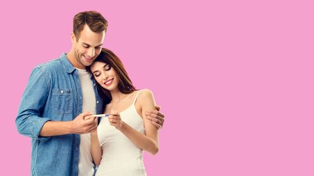 Love, relationship, new parents and happy family concept - young couple, finding out results of a pregnancy test. Over rose pink background. Copy space for some text.