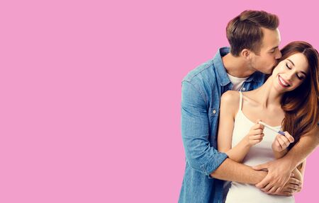 Love, relationship, happy lovers, family concept - amorous happy couple, finding out results of a pregnancy test. Rose pink color background. Copy space for text.