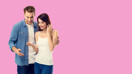 Love, new parents and happy family concept - young happy couple, finding out results of a pregnancy test. Over rose pink color background. Copy space for some text.