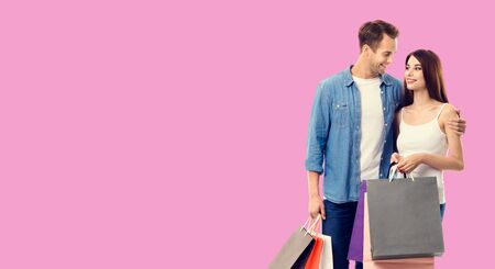 Love, holiday sales, shop, retail, consumer concept - happy couple with shopping bags, looking at each other. Over rose pink color background. Copy space for some text. 스톡 콘텐츠