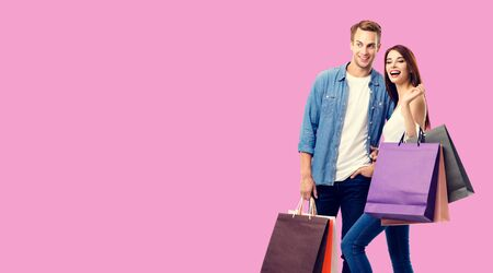 Love, holiday sales, shop, retail, consumer concept - happy couple with shopping bags, standing close to each other. Over rose pink background. Copyspace for some text. 스톡 콘텐츠
