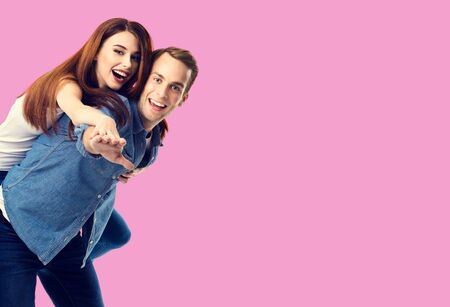 Love, relationship, dating, lovers, romantic concept - happy excited couple, in piggyback pose, against rose pink background. Copy space for some text.