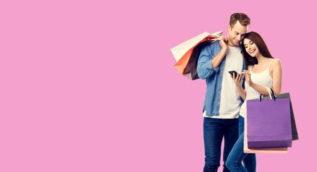 Love, holiday sales, shop, retail, consumer concept - happy couple with shopping bags, looking at mobile phone, standing close to each other. Over rose pink color background.