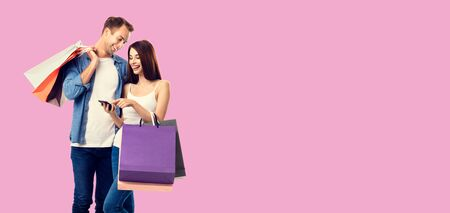 Love, holiday sales, shop, retail, consumer concept - happy smiling couple with shopping bags, and cellphone, standing close to each other. Over rose pink color background.