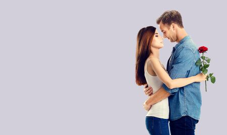 Love, relationship, dating, flirting, romantic concept - amorous hugging couple with flower, standing close to each other, against grey background. Copy space.