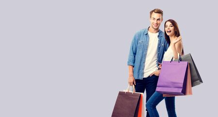 Love, holiday sales, shop, retail, consumer concept - happy couple with shopping bags, standing close to each other. Over grey background. Copyspace for some text.