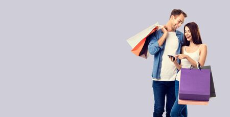 Love, holiday sales, shop, retail, consumer concept - happy smiling couple with shopping bags, and cellphone, standing close to each other. Over grey background.