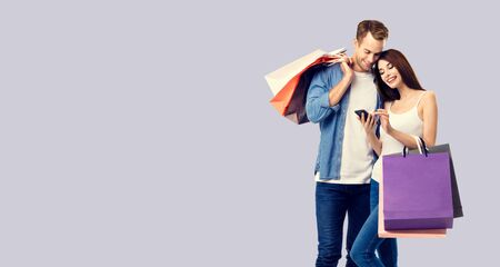 Love, holiday sales, shop, retail, consumer concept - happy couple with shopping bags, looking at mobile phone, standing close to each other. Over grey background. 스톡 콘텐츠