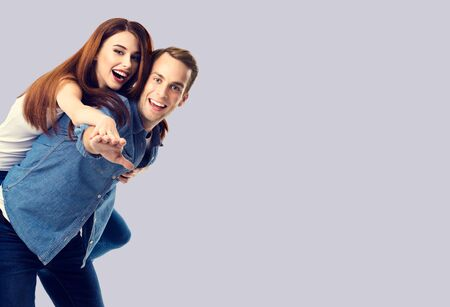 Love, relationship, dating, lovers, romantic concept - happy excited couple, in piggyback pose, against grey background. Copy space for some text.
