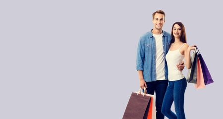 Love, holiday sales, shop, retail, consumer concept - happy couple with shopping bags, standing close to each other, and looking at camera. Grey color background. 스톡 콘텐츠