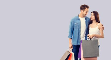 Love, holiday sales, shop, retail, consumer concept - happy couple with shopping bags, looking at each other. Over grey background. Copy space for some text.