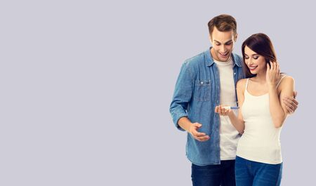 Love, new parents and happy family concept - young happy couple, finding out results of a pregnancy test. Over grey background. Copy space for some text.