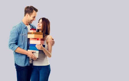 Love, relationship, dating, flirting, lovers, romantic concept - happy young couple holding gift boxes, close to each other. Grey color background. Copy space for text.