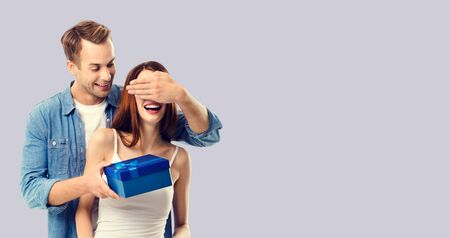 Love, dating, celebrating, lovers concept - happy amorous couple with blue gift box. Over grey background. Copy space for some text. 스톡 콘텐츠
