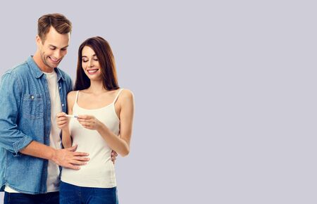 Love, relationship, new parents and happy family concept - young lovely couple, finding out results of a pregnancy test. Over grey background. 스톡 콘텐츠