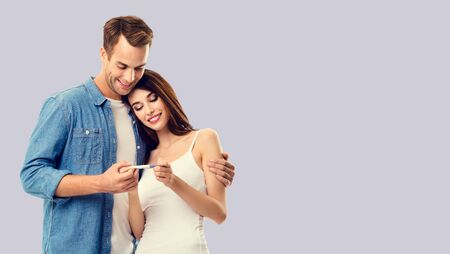 Love, relationship, new parents and happy family concept - young couple, finding out results of a pregnancy test. Over grey background. Copy space for some text.