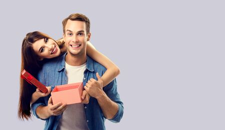Love, relationship, dating, flirting, lovers, romantic concept - happy couple opening gift box, looking at camera. Over grey color background. Copy space for some text. 스톡 콘텐츠