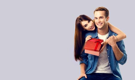 Love, relationship, dating, flirting, lovers concept - happy smiling amorous couple opening gift box. Over grey background. Copy space for some text. 스톡 콘텐츠