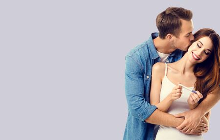 Love, relationship, happy lovers, family concept - amorous happy couple, finding out results of a pregnancy test. Grey color background. Copy space for text.