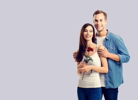 Love, relationship, dating, flirting, romantic concept - portrait of young happy smiling hugging couple with flower, close to each other. Over grey background.