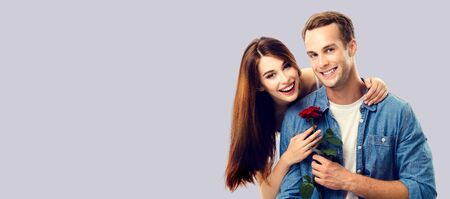 Love, relationship, dating, flirting, romantic concept - portrait picture of happy couple with flower, looking at camera. Over grey background. Copy space for some text.